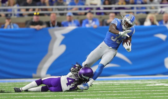 Lions running back Kerryon Johnson is tackled against the Vikings in the first half.