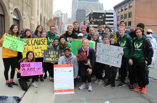 Wayne State University swimming and diving team members surround Adrianna Waack in the reunion area on Fort St. after she completed the Detroit Free Press/TCF Bank Marathon on Sunday, Oct. 20, 2019.