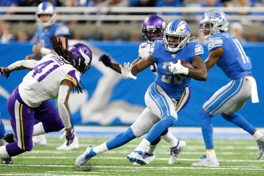 Lions running back Kerryon Johnson runs the ball against Vikings defensive back Anthony Harris during the first quarter Sunday.
