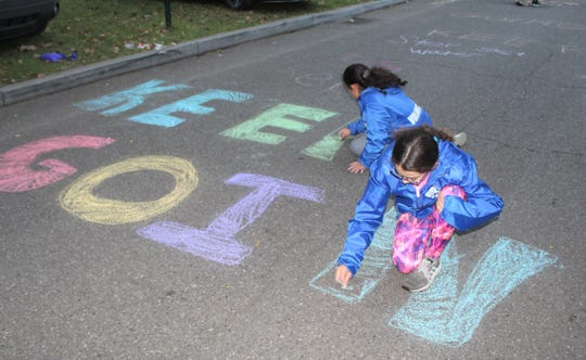 Eleven-year-old Girl Scouts Eden Bishai and Clare Antaki chalk a motivational message on the pavement near the Indian Village aid station on Burns during the 2019 Detroit Free Press/TCF Bank Marathon on Sunday, Oct. 20, 2019.