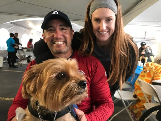 Omar Duran celebrates Sunday with wife, Jill Duran, and service dog Tyse after taking second in the Detroit marathon's Disabilities Division.