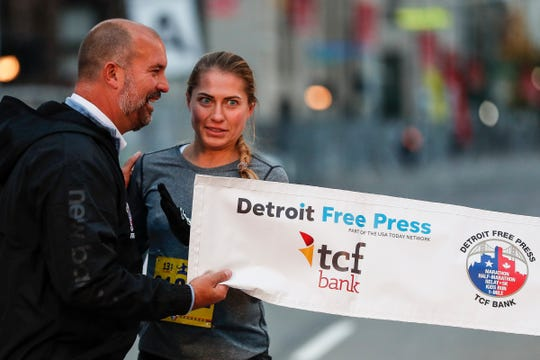 Pelageya Budankova talks to Tim Gruber at the finish line during the 42nd Annual Detroit Free Press/TCF Bank Marathon in Detroit on Sunday, Oct. 20, 2019.