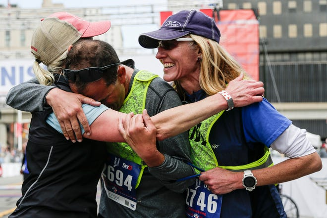Marathoner Richard Bernstein of Birmingham, center, is congratulated by his guides Mandy Jellerichs of Annapolis, Md. left, and Sara Reichert of Plymouth, right, after they cross the finish line during the 42nd Annual Detroit Free Press/TCF Bank Marathon in Detroit on Sunday, Oct. 20, 2019.