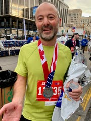 Brian Zanier, 46, shows off his bloody palm after stumbling just before the finish line at the Detroit Free Press/TCF Bank Marathon on Sunday, Oct. 20, 2019.