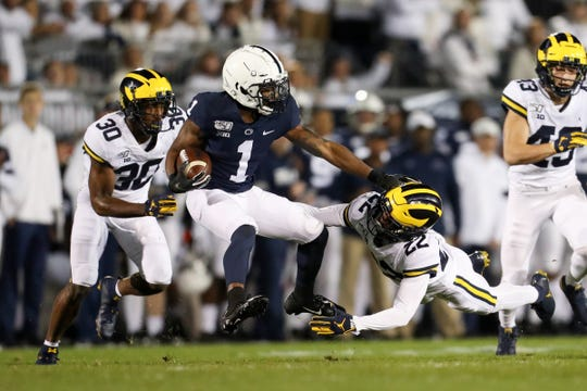 Penn State receiver KJ Hamler runs with the ball while trying to avoid a tackle from Michigan defensive back Gemon Green (22) during the first quarter at Beaver Stadium, Oct. 19, 2019.