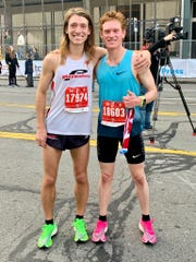 Lansing-area runners Juris Silenieks, left, and Scott Lieberman celebrate first- and third-place finishes, respectively, during the 42nd Detroit Free Press/TCF Bank international half-marathon Sunday, Oct. 20, 2019.