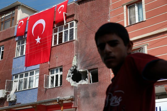 A child stands across from a building damaged by a mortar fired from inside Syra, in Akcakale, Sanliurfa province, southeastern Turkey, Sunday, Oct. 13, 2019. Incoming shells fired from northeastern Syria hit the house earlier on Sunday. Two residents were at the house and were evacuated.