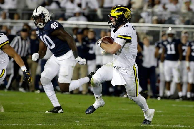Michigan quarterback Shea Patterson, right, runs for a first down against Penn State.