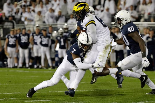 Penn State safety Jaquan Brisker (7) tackles Michigan tight end Nick Eubanks (82) during the first half on Saturday.