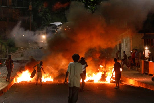 Demonstrators set up burning barricades to block a street during a protest demanding the resignation of President Juan Orlando Hernandez, in Tegucigalpa, Honduras, late Friday, Oct. 18, 2019.