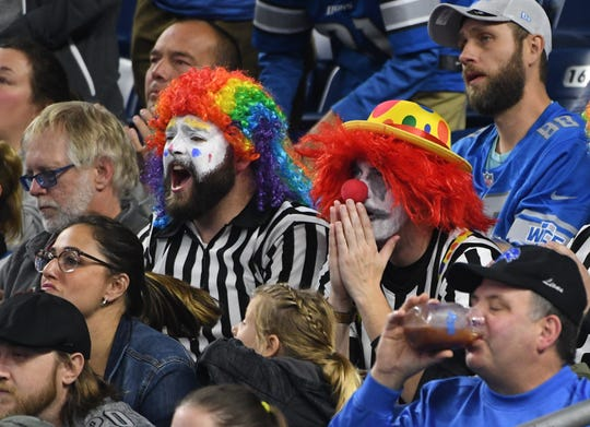 Fans dressed in referee clown outfits sit quietly as the Vikings slowly take down the Lions in a 42-30 loss Sunday at Ford Field in Detroit.