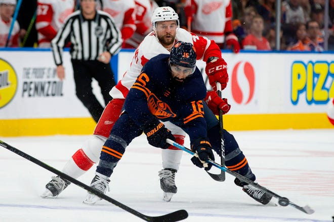Oilers left wing Jujhar Khaira (16) tries to control the puck as Red Wings center Luke Glendening (41) defends during the second period Friday in Edmonton.
