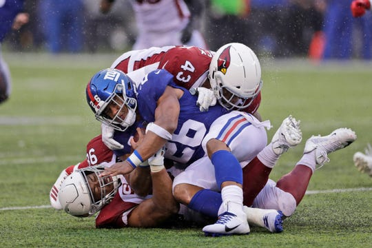 Giants' Saquon Barkley, center, is brought down by a pair of Cardinals defenders during the second half on Sunday.