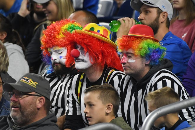 Fans dressed in referee clown outfits sit quietly as the Vikings slowly take down the Lions in a 42-30 loss Sunday at Ford Field.