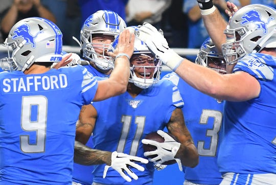 Marvin Jones celebrates with teammates Matthew Stafford and Frank Ragnow after a touchdown against the Vikings.