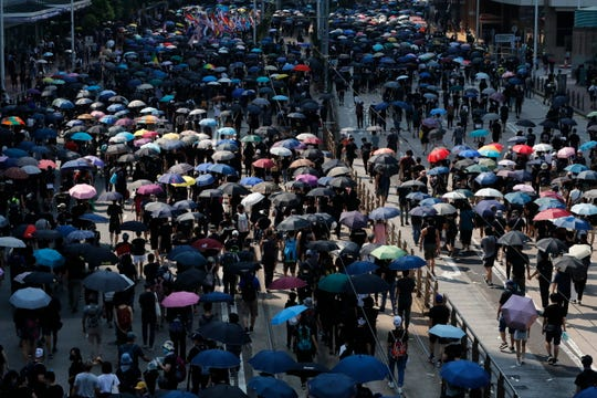 "Anti-government protesters holding umbrellas march past police headquarters in Hong Kong, Tuesday, Oct. 1, 2019. Thousands of black-clad pro-democracy protesters defied a police ban and marched in central Hong Kong on Tuesday, urging China's Communist Party to ""return power to the people"" as the party celebrated its 70th year of rule."