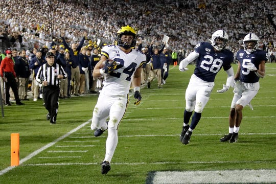 Michigan running back Zach Charbonnet (24) runs into the end zone for a touchdown past Penn State defensive end Jayson Oweh (28) and cornerback Tariq Castro-Fields (5) during the first half.