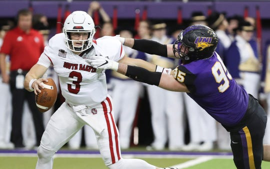 South Dakota quarterback Austin Simmons tries to break a tackle by Northern Iowa defensive end Seth Thomas in a 42-27 loss on Oct. 19, 2019.