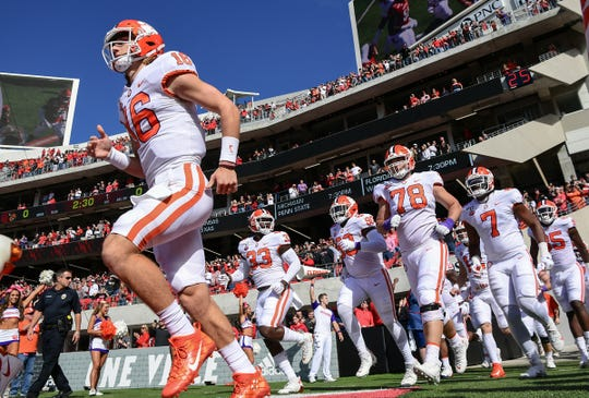 Clemson quarterback Trevor Lawrence (16) runs on the field with teammates before the game at Cardinal Stadium in Louisville, Kentucky Saturday, October 19, 2019.