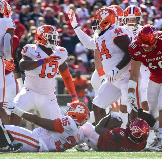 Clemson defensive lineman Tyler Davis(13), left, defensive tackle Nyles Pinckney (44) celebrate after linebacker Justin Foster (35) tackled Louisville running back Javian Hawkins(10) during the second quarter at Cardinal Stadium in Louisville, Kentucky Saturday, October 19, 2019.