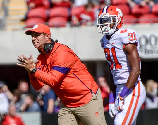 Clemson Head Coach Dabo Swinney communicates with players near Clemson defensive back Mario Goodrich (31) during the third quarter at Cardinal Stadium in Louisville, Kentucky Saturday, October 19, 2019.