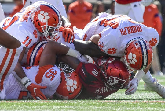 Clemson linebacker Justin Foster (35) safety Isaiah Simmons (11), and defensive end Logan Rudolph(34) tackle Louisville running back Javian Hawkins(10) during the second quarter at Cardinal Stadium in Louisville, Kentucky Saturday, October 19, 2019.