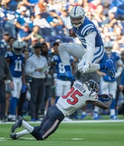 Eric Ebron of the Indianapolis Colts leaps over Keion Crossen of the Houston Texans during second half action, Houston at The Colts, Lucas Oil Stadium, Indianapolis, Sunday, Oct. 20, 2019. Colts won 30-23 to pull ahead in the race for the AFC South title.