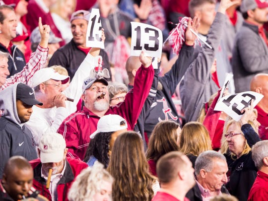 Alabama fans light up cigars and hold up signs with 13 on them during Tennessee's game against Alabama at Bryant-Denny Stadium in Tuscaloosa, Ala., on Saturday, October 19, 2019.
