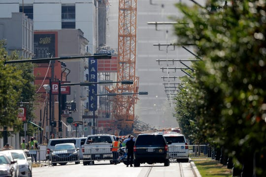 Two large cranes from the Hard Rock Hotel construction collapse come crashing down after being detonated for implosion in New Orleans, Sunday, Oct. 20, 2019. A large piece of one flipped off the building and landed top-first on Rampart Street outside the French  Quarter.