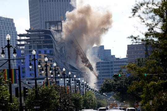 Two large cranes from the Hard Rock Hotel construction collapse come crashing down after being detonated for implosion in New Orleans, Sunday, Oct. 20, 2019. New Orleans officials set off several explosions Sunday intended to topple two cranes that had been looming over the ruins of a partially collapsed Hard Rock Hotel. (AP Photo/Gerald Herbert)