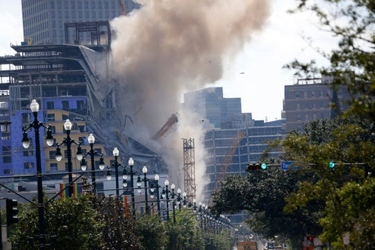 Two large cranes from the Hard Rock Hotel construction collapse come crashing down after being detonated for implosion in New Orleans, Sunday, Oct. 20, 2019. (AP Photo/Gerald Herbert)