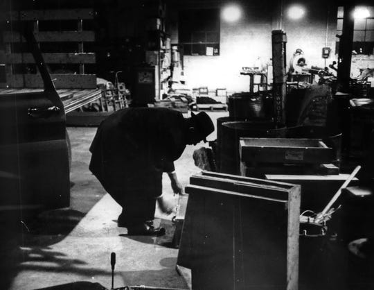 An investigator crouches over the spot where the body of Diane Olkwitz was found inside Kenworth Manufacturing Co. in Menomonee Falls on Nov. 3, 1966.