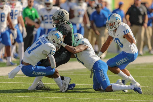 North Texas' Jyaire Shorter (16) is tackled by MTSU's Kylan Stribling (17) and Terelle West (1) during the Blue Raiders 33-30 loss to the Mean Green on October 19, 2019.