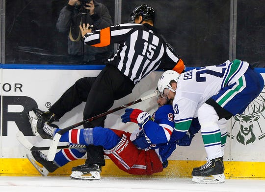 New York Rangers center Mika Zibanejad (93) and Vancouver Canucks defenseman Alexander Edler (23) collide with the referee during the second period at Madison Square Garden.