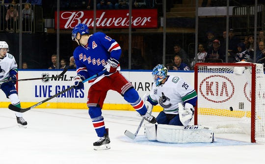 New York Rangers right wing Jesper Fast (17) deflects the puck past Vancouver Canucks goaltender Jacob Markstrom (25) for a goal during the second period at Madison Square Garden.