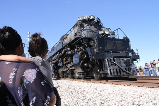 Over the shoulders of Jessica Madrid and Danaeh Acosta, 2, is the world's largest steam locomotive, Union Pacific's Big Boy No. 4014. Big Boy No. 4014 made a brief stop in Deming, New Mexico.