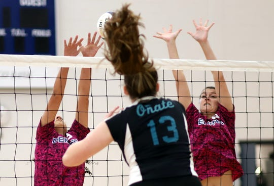 Lady 'Cat Katie Morgan, right, and teammate Briana Flores put up a block against Onate's Lauren Martin (13).