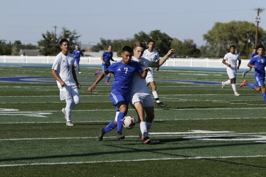 Carlsbad's Louis Ruiz battles a Roswell player in the first half of their match Oct. 19, 2019. Ruiz recorded an assist in the game but Roswell won, 3-1.