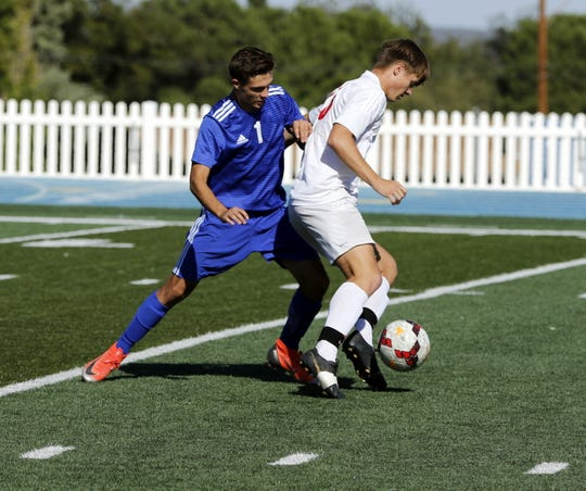 Carlsbad's Jarek Castillo battles a Roswell player for possession in the first half of their match Oct. 19, 2019. Roswell won, 3-1.