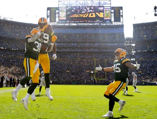 Green Bay Packers running back Jamaal Williams (30) celebrates a second quarter touchdown with tight end Marcedes Lewis (89) and fullback Danny Vitale (45) against the Oakland Raiders during their football game Sunday, October 20, 2019, at Lambeau Field in Green Bay, Wis.