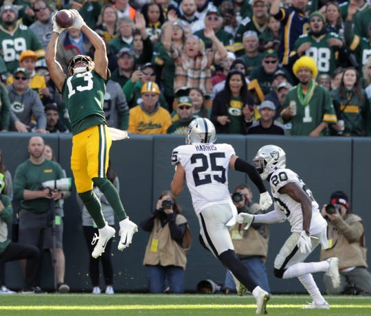 Green Bay Packers wide receiver Allen Lazard (13) halls in a pass from quarterback Aaron Rodgers (12) against the Oakland Raiders during their football game Sunday, October 20, 2019, at Lambeau Field in Green Bay, Wis.