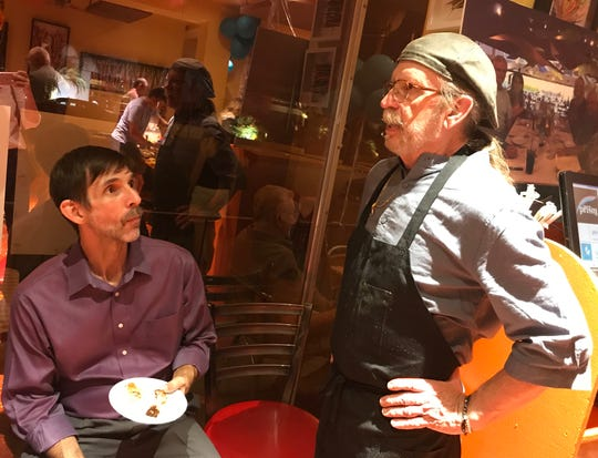 John Telles, operations manager for Bill's Pizza, speaks with chef Steven Helland, at the public memorial Bill Tracy, founder of the Palm Springs restaurant, on Oct. 19, 2019.