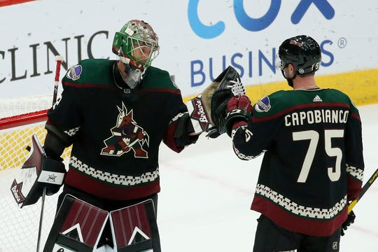 Arizona Coyotes goaltender Antti Raanta, left, celebrates with defenseman Kyle Capobianco (75) as time expires in the third period of an NHL hockey game win against the Ottawa Senators, Saturday, Oct. 19, 2019, in Glendale, Ariz. (AP Photo/Ross D. Franklin)
