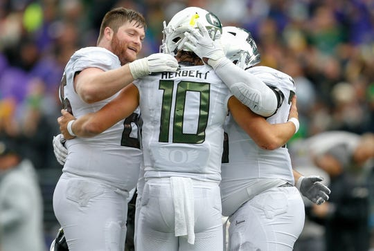 Oregon offensive lineman Brady Aiello (left) hugs quarterback Justin Herbert (10) after a win against Washington on Oct. 19 at Husky Stadium.