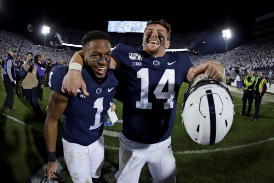 Penn State quarterback Sean Clifford (14) and wide receiver KJ Hamler celebrate the team's 28-21 win over Michigan in an NCAA college football game in State College, Pa., Saturday, Oct. 19, 2019. (AP Photo/Gene J. Puskar)