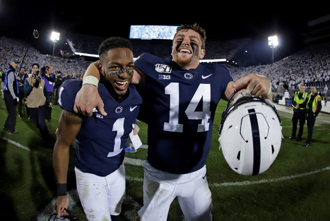 Penn State quarterback Sean Clifford (14) and wide receiver KJ Hamler celebrate the team's 28-21 win over Michigan in an NCAA college football game in State College, Pa., Saturday, Oct. 19, 2019. (AP Photo/Gene J. Puskar)