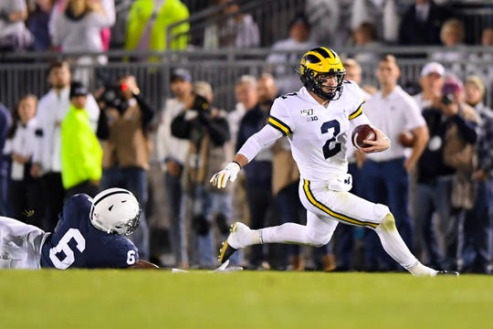 Oct 19, 2019; University Park, PA, USA; Michigan Wolverines quarterback Shea Patterson (2) runs with the ball past Penn State Nittany Lions linebacker Cam Brown (6) during the first quarter at Beaver Stadium. Mandatory Credit: Rich Barnes-USA TODAY Sports