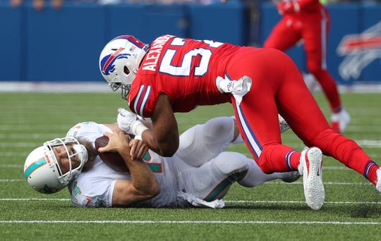 Miami quarterback Ryan Fitzpatrick is tackled by Buffalo's Lorenzo Alexander after a short gain.