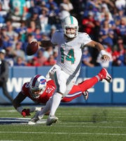 Miami quarterback Ryan Fitzpatrick scrambles away from pressure by Buffalo's Jerry Hughes.