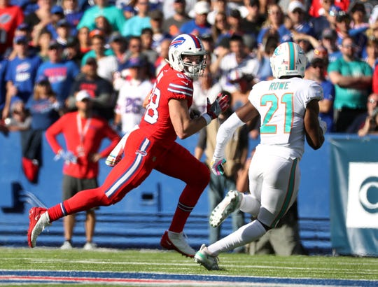 Bills tight end Dawson Knox looks to beat Miami's Eric Rowe after a catch.